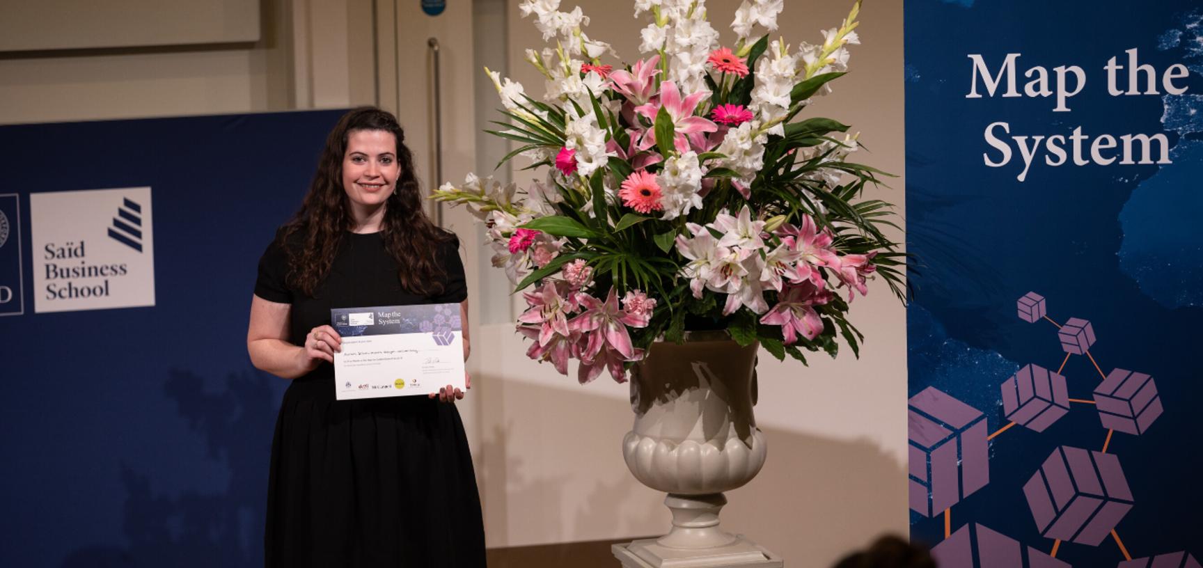 Roisin Dillon, Mount Royal University, holding Map the System 2018 Prize award