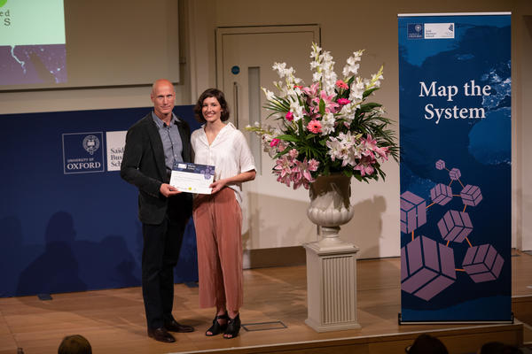 Dr. Abbey Eeles, University of Melbourne, holding Map the System 2018 prize award
